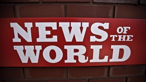 A News of the World sign is posted by an entrance of its parent company in London. News Corp. executive James Murdoch announced Thursday that News of the World will publish its last issue Sunday. A phone-hacking scandal has cost the weekly paper prestige and prompted dozens of companies to pull their ads. (AP)
