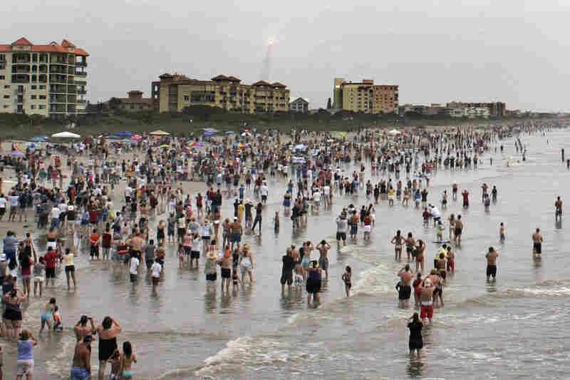 Thousands gather in the surf and on the sand at Cocoa Beach, Fla.