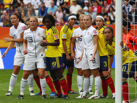 U.S. players, in white, line up for a corner kick against Colombia in a group stage game of the 2011 Women's World Cup. The white jerseys have been criticized as resembling a nurse's uniform.