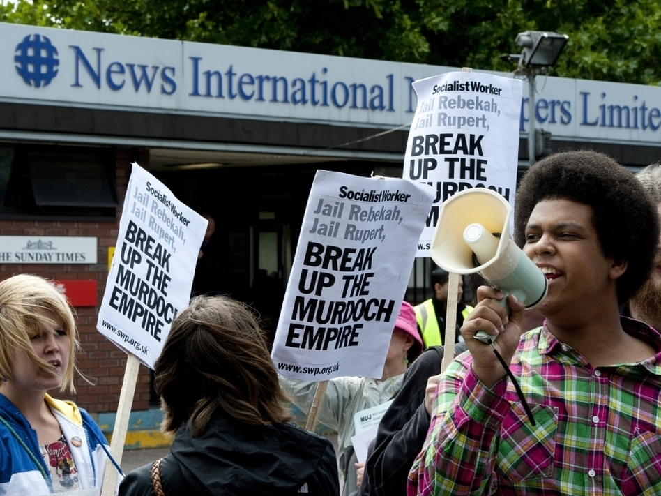 Demonstrators protest outside the headquarters of News International in London on Friday as Prime Minister David Cameron promised inquiries into a phone hacking scandal.