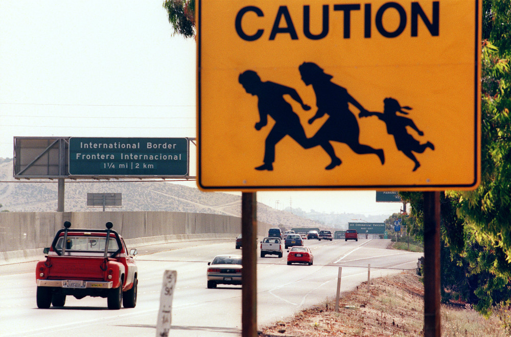 A 1997 photo shows a sign in San Diego, Calif., warning drivers about pedestrians running across the highway at the U.S.-Mexico border. St. John says that seeing borders as tools to control the movement of people is a uniquely 20th-century phenomenon.