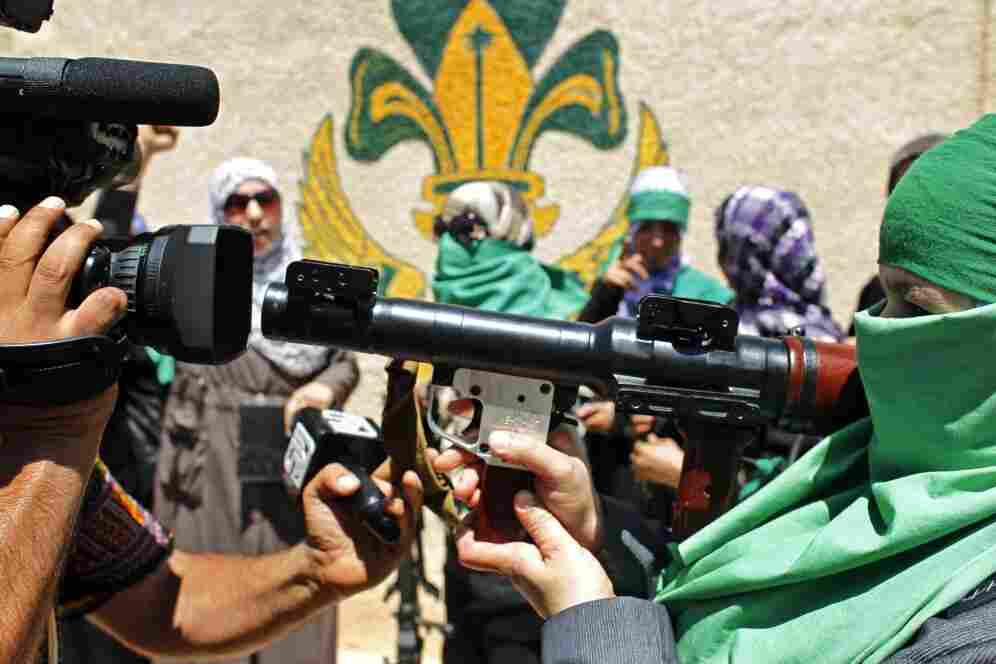 A journalist  videotapes a Libyan woman as she points her weapon at the camera in Gharyan, a city south of Tripoli. Moammar Gadhafi's regime organized a demonstration Sunday for reporters to try to show it remains in control of parts of the  country's western mountains and will defend the territory against  further rebel advances.