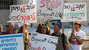 "Israeli activists hold signs as they demonstrate against the suggested ""boycott law"", in front of the Justice ministry in east Jerusalem on July 10."
