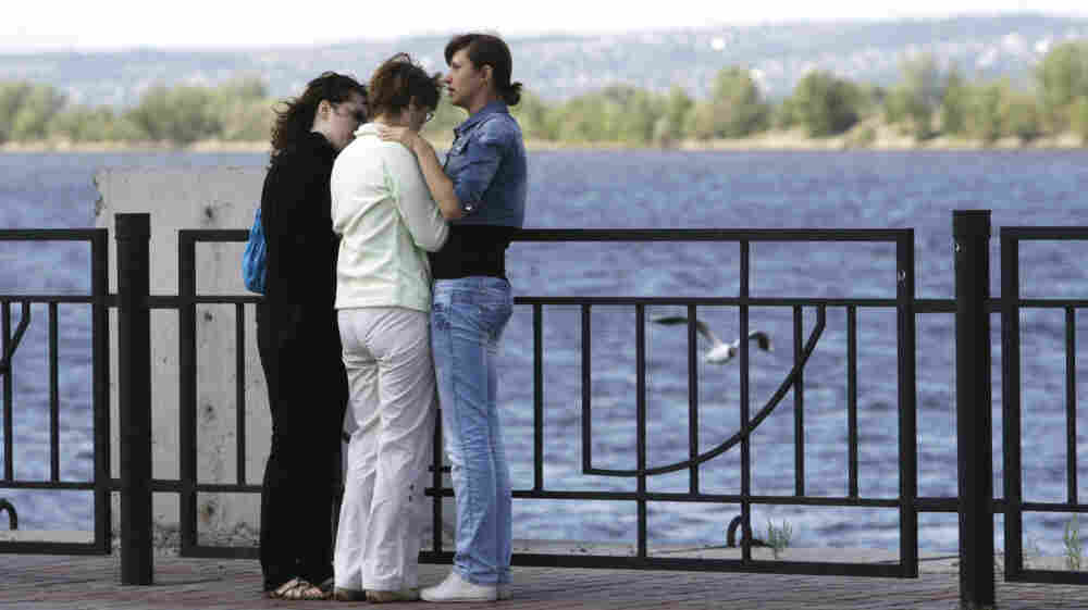 Relatives of passengers believed to be aboard a cruise ship that sank on the Volga River await fresh information at a river station in Kazan, about 450 miles east of Moscow on Monday. More than a dozen had been confirmed dead Monday morning, and more than 100 remained missing.