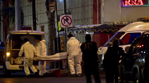 Forensic workers load a truck with bodies after gunmen opened fire in a nightclub in Monterrey, Mexico, Friday July 8, 2011.