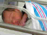 A photo of a newborn in the hospital with the standard pink-and-blue striped receiving blanket.