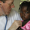 Paul Farmer examines a child at a mobile clinic in Haiti.