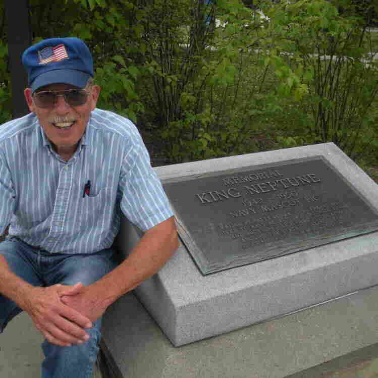 """Jim Goddard, a retired shop owner from Anna, Ill., sits next to a plaque dedicated to his grandpa's pig, King Neptune. The plaque reads: """"King Neptune: 1942 to 1950. Navy Mascot Pig."""""""