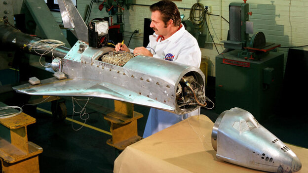 A worker tests components on a model of the space shuttle before wind tunnel testing.