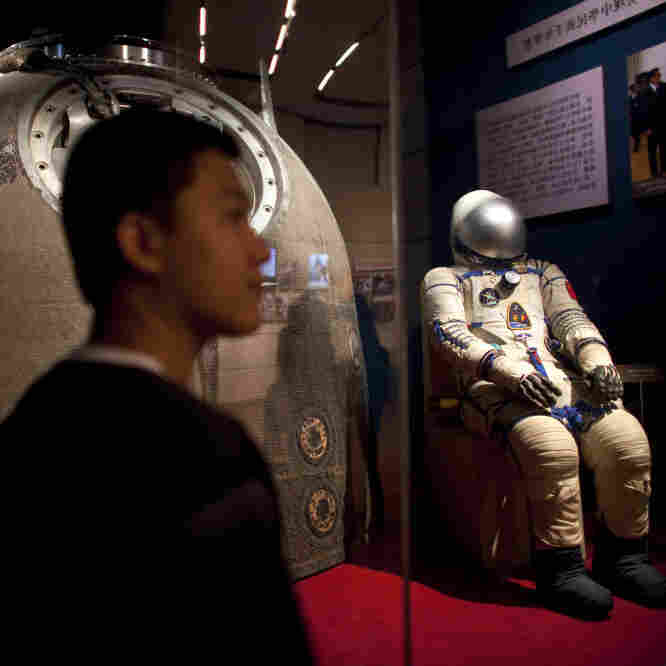 A visitor stands near the Shenzhou 5 re-entry capsule, used in China's first human spaceflight mission, and the spacesuit worn by crew member Yang Liwei, at an exhibition in Beijing on July 6.