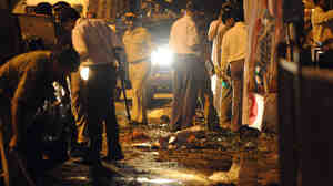 Indian police officers look for clues at the blast site in Dadar Kabutarkhana area, in Mumbai.