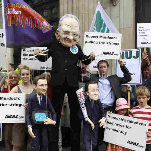 Demonstrators, one wearing a mask depicting Rupert Murdoch (center), holds puppets depicting British Prime Minister David Cameron (right) and British Culture Minister Jeremy Hunt (left) as they protest outside the Department of Culture Media and Sport in central London on Thursday to show their opposition to the proposed sale of BSkyB to Murdoch's News International.