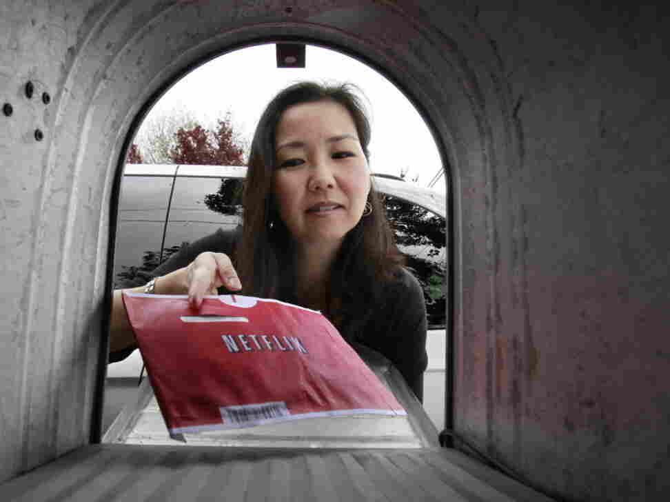 Carleen Ho picks up a movie from her mailbox in Palo Alto, Calif.