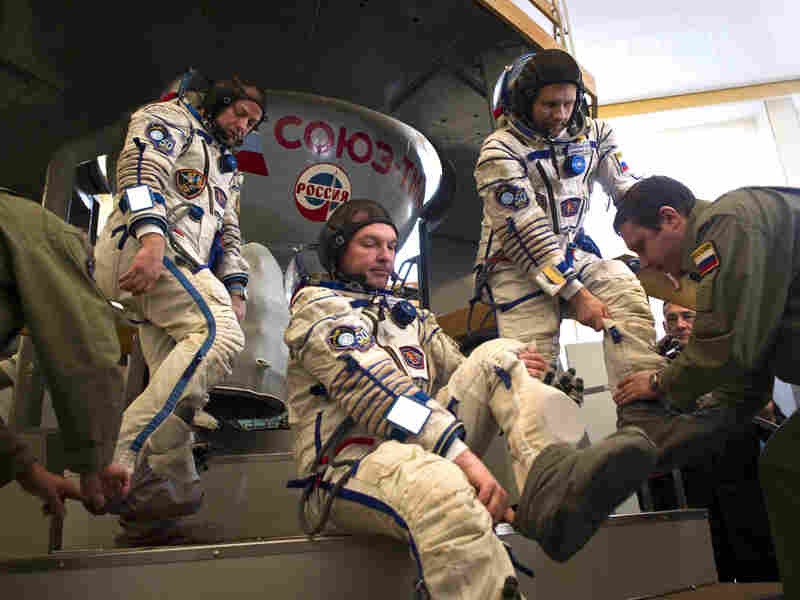 Crew members of the International Space Station — (from left) U.S. astronaut Ron Garan and Russian cosmonauts Alexander Samokutyaev and Andrei Borisenko — prepare to enter a Soyuz simulator outside Moscow on March 30. With the space shuttle program out of commission, the Russian Soyuz vehicle will be the only way for Americans to reach space.