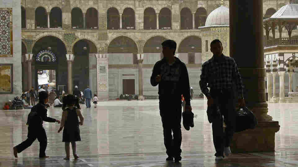 Syrians walk outside the Omayyad Mosque in Damascus in April. Residents are adapting to life amid the ongoing uprising against President Bashar Assad's regime.