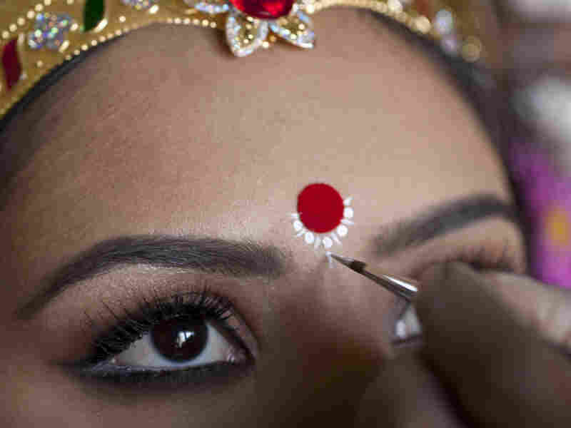 A make-up artist studied and painted the features of Maa  Laxmi's eyes and ornamental touches.