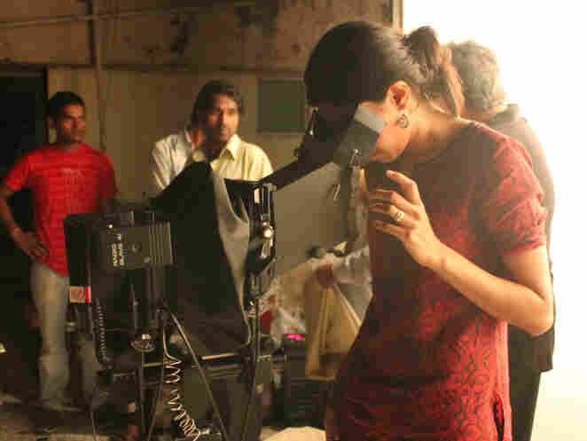Sharma peers through her large-format camera on set.
