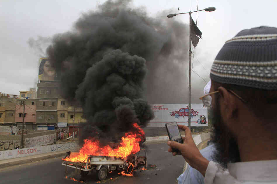 A man takes pictures of a vehicle burned by angry protesters in Karachi, Pakistan.