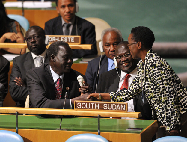 The South Sudan delegation, including Vice-President Riek Machar Teny-Dhurgon (second from right), are congratulated by a delegate as they take their seats after the U.N. General Assembly voted to admit the newl