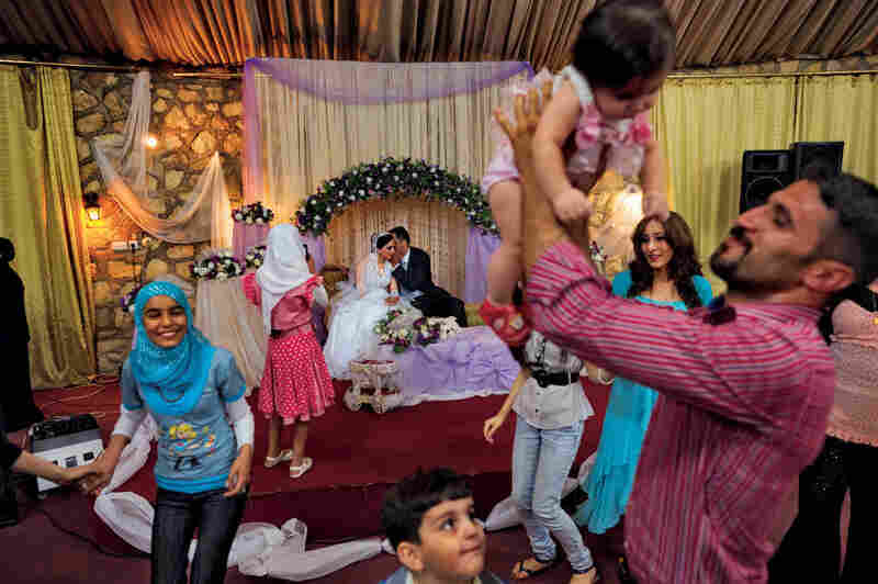 "Weddings costing up to $10,000 have become more common in Baghdad, as young people feel safe enough to plan for the future. Some 300 guests celebrated for two days when bride Heelan Muhammad married Husham Raad last October. Daily life isn't always easy, says Raad Ezat-Khalil (with baby), the groom's cousin and matchmaker, but ""the most important thing is how strong and determined people are."""