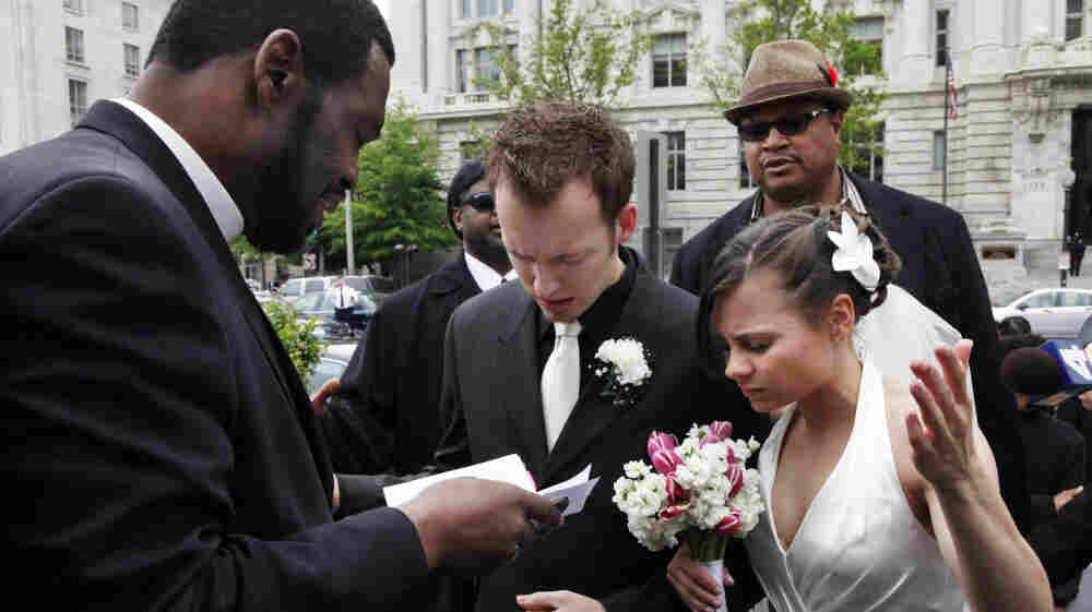 Bishop Harry R. Jackson Jr., left, prays with Jonathan Paul Ganucheau and Denise Buckbinder Ganucheau before performing a religious wedding ceremony that was part of a protest against the District of Columbia city council's approval of legislation recognizing same sex marriages performed in other states, in Washington, on Tuesday, May 5, 2009.