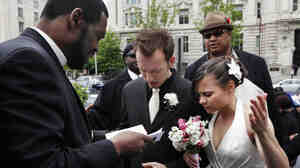 Bishop Harry R. Jackson Jr., left, prays with Jonathan Paul Ganucheau and Denise Buckbinder Ganucheau before performing a religious wedding ceremony that was part of a protest against the District of Columbia city council's app