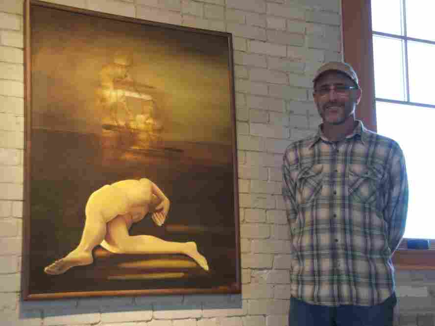 "Dr. Bill Blahd poses in front of one of his paintings: ""Recurring Daymare."" Blahd says he he hopes to illustrate feelings that are hard to verbalize through his paintings."