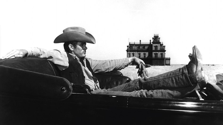 James Dean on the set of the 1956 film <em>Giant</em>, which was filmed on the Ryan Ranch, west of the town of Marfa. The skeleton of the mansion in the background still stands on the ranch today. (Warner Bros. Pictures/Photofest)