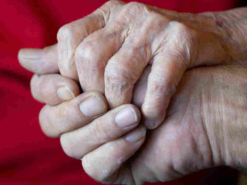 A son holding his elderly mother's hand.