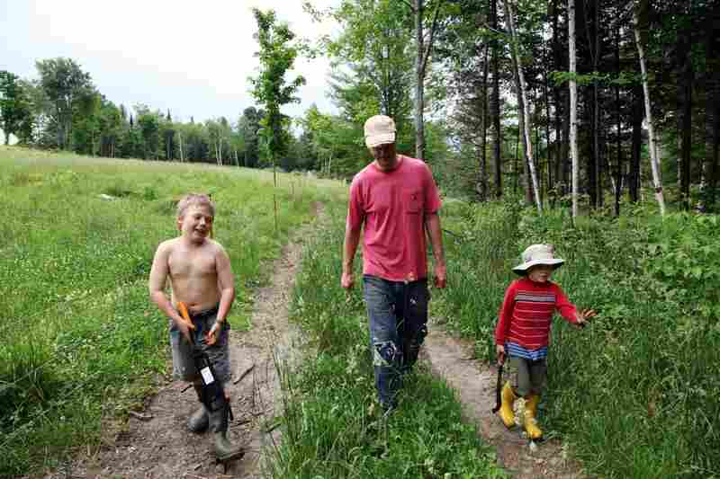 The Hewitt boys, Fin (left) and Rye (right), walk with their father on the family farm. Hewitt is a back-to-the land activist who helped put Hardwick's local food scene on the map.