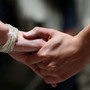 A same-sex couple holds hands.
