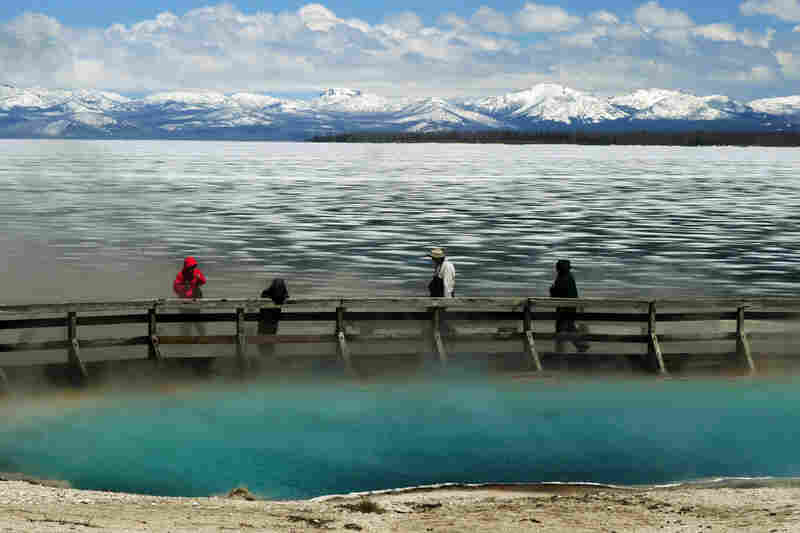 Tourists walk beside a hot spring and the partially frozen Yellowstone Lake at the West Thumb Geyser Basin.