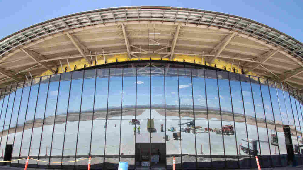 The San Andres Mountains and pieces of construction equipment are  reflected in the glass windows of Spaceport America near Upham, N.M., in  May. Despite construction delays and difficult working conditions in a  remote area of the desert, state officials say New Mexico is committed  to seeing the project succeed.