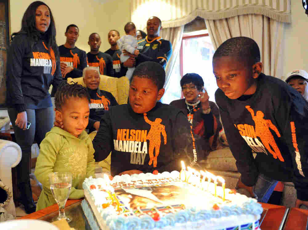 Former president Nelson Mandela, second from left center, and his extended family members celebrate his 93rd birthday in Qunu, South Africa, Monday July 18, 2011.