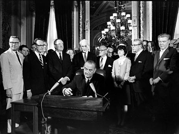 President Lyndon B. Johnson signs the Voting Rights Act into law. One provision of the law is still controversial.