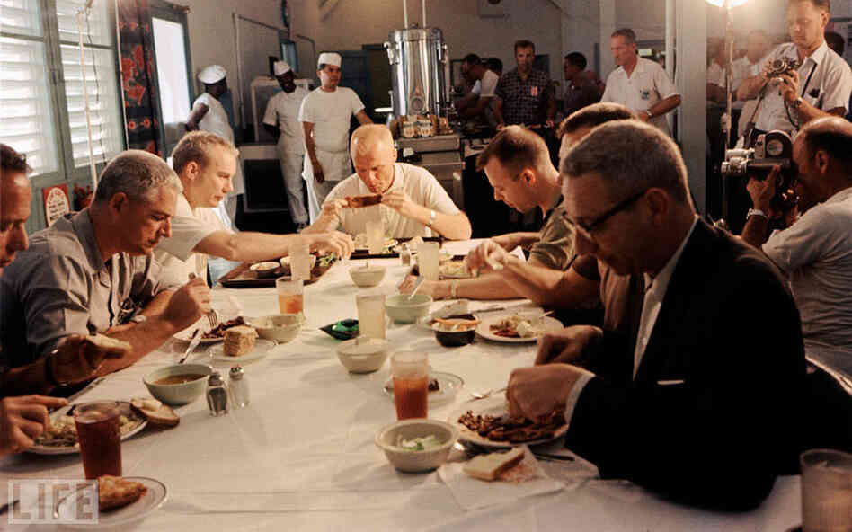 Glenn eats a meal, surrounded by media, prior to his historic February 1962 orbital flight.