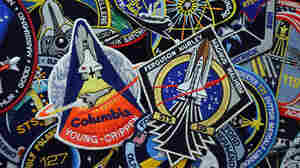 Every space shuttle mission had its own mission emblem, designed and worn by the crews. Centered in this photo are the embroidered patches for the first and last missions, STS-1 and STS-135. The STS-1 emblem is a rare version, produced only for the astronauts and NASA employees. The souvenir edition was slightly different.