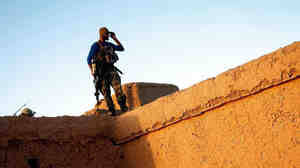 Afghan National Army soldier Mohammed Shadwar gets a bird's-eye view from the rooftop of a mud-walled compound during a joint clearing operation in Helmand province, Afghanistan. As the top U.S. commander in Afghanistan changes, there's a question of whether U.S. policy will shift from one that supports building up Afghan national security forces to one focused on targeting insurgents.
