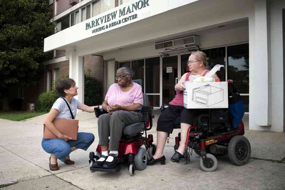 Hendrix waits for transportation to her new apartment with Toni Pastore, a paralegal from Atlanta Legal Aid Society, who organized her relocation (left), and Cheryl Laurendeau, her peer supporter.