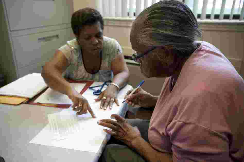 Selena Rambert, manager for Capitol Avenue Apartments, goes over paperwork with Hendrix before she moves into the apartment that will be her new home.