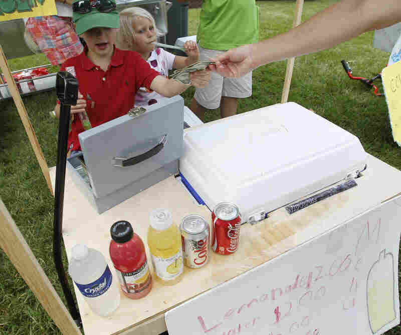 Young entrepreneurs collect money at their lemonade stand outside the site of the U.S. Open Championship golf tournament in June in Montgomery County, Md.