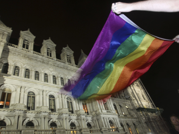 Robert Moore waves a gay pride flag outside the Capitol in Albany, N.Y., after the state Senate passed a bill legalizing same-sex marriage on June 24.
