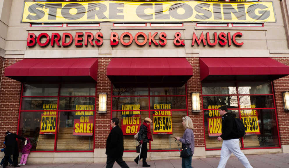 Pedestrians pass by a Washington, DC Borders book store with signs announcing it was closing: March 4, 2011.