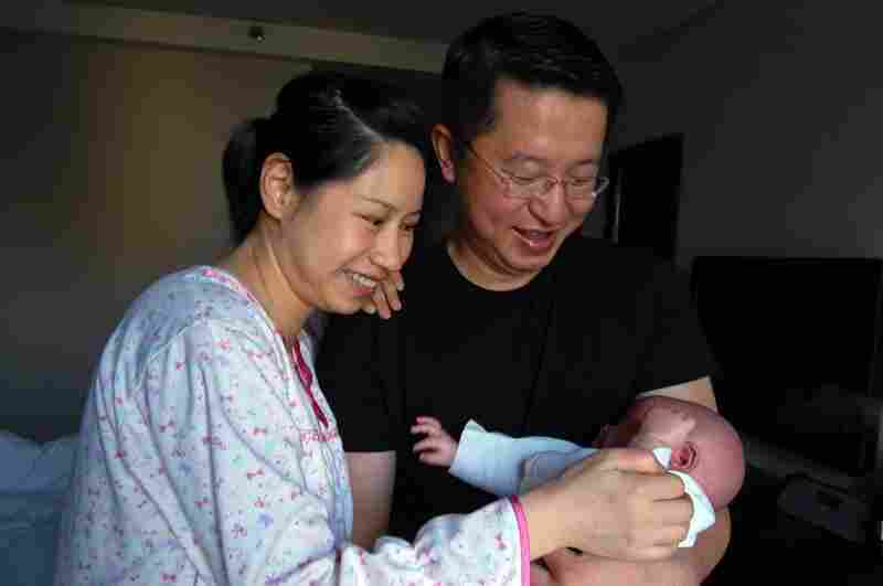 "New parents Wu Lili (left) and Mo Shiwei hold their 29-day-old baby boy, nicknamed Momo, at the Weige Center in Beijing. The new mother is participating in the Chinese tradition of ""sitting the month,"" in which she follows certain rules, such as not going outside, not washing her hair or showering, and only eating certain foods."