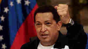 Chavez raises a fist as he holds a copy of a newspaper in a Caracas airport on July 4, after returning from Cuba where he had surgery to remove a cancerous tumor.