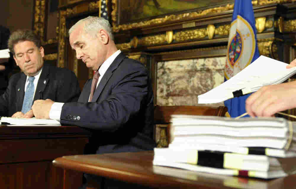 Minnesota Gov. Mark Dayton signs the state budget bill to end his government's shutdown as Secretary of State Mark Ritchie watches, Wednesday, July 20, 2011.