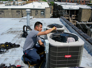 """Eric Rebolledo, a repairman for AllTemp heating and air conditioning in Chicago, works on an air-conditioning unit on the roof of an apartment building. """"I don't remember it being this hot for at least 10 years that I can recall,"""" he says. """"This is unusual, man, so it's gonna create some havoc"""
