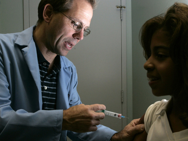 Dr. Donald Brown, left, gives 14-year-old Kelly Kent a dose of Gardasil, a vaccine for the human papillomavirus in 2006. The group that advises the U.S. government on vaccination recommendations is now starting to take costs for vaccines like Gardasil into consideration as vaccine prices rise.