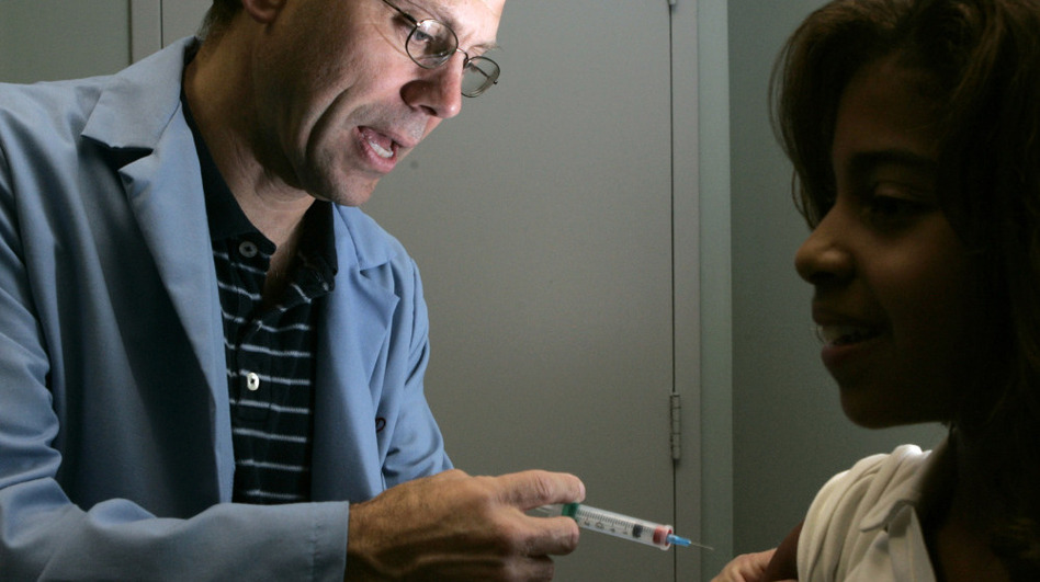 Dr. Donald Brown, left, gives 14-year-old Kelly Kent a dose of Gardasil, a vaccine for the human papillomavirus in 2006. The group that advises the U.S. government on vaccination recommendations is now starting to take costs for vaccines like Gardasil into consideration as vaccine prices rise. (AP)