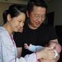 "New parents Wu Lili (left) and Mo Shiwei hold their 29-day-old baby boy. The new mom is staying at the Weige center in Beijing, which provides luxury accommodation and 24-hour nursing staff to woman who are participating in the Chinese tradition of ""sitting the month."""